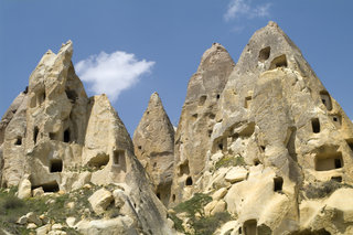 "CAPPADOCIA, UçHISAR, TURKEY - 2010/04/17: Fairy chimneys filled with houses near the village of Uçhisar in Cappadocia, Turkey. The landscape in Cappadocia is formed from compacted volcanic ash called ""tuff"" that smothered the land some 30 million years ago. Natural forces have since sculpted a wonderland of ridges, canyons and bizarre phallic protrusions known as fairy chimneys. People have been dugging caves for houses in the soft stone since prehistoric times. (Photo by Leisa Tyler/LightRocket via Getty Images)"